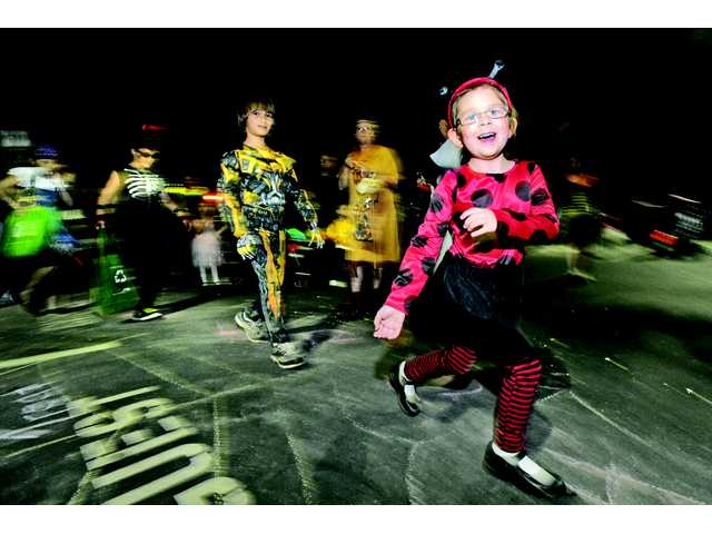 Aubrey Hubbard, 5,  right, of Castaic dressed as a ladybug, marches in the spider walk at the Fall Festival in Valencia.