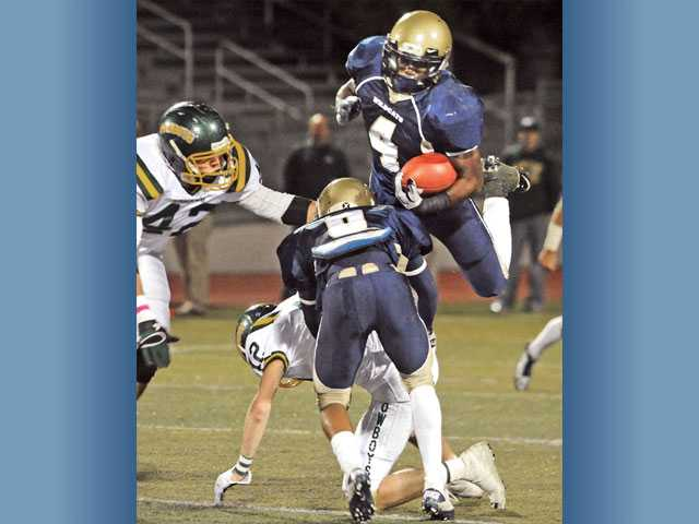 West Ranch running back Jeff Coprich (4) dives for extra yardage over Canyon defender Andre Beets (12) while Canyon's Robert Hooper (42) looks on during the first quarter on Friday night at Valencia High School.