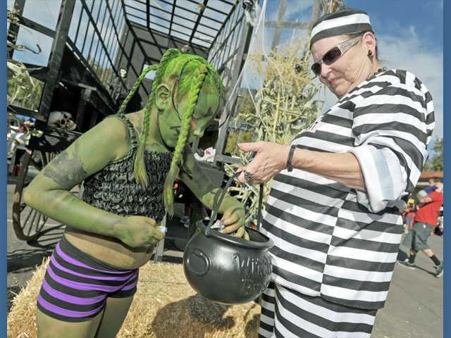 Sandra Reese, right, hands candy to Vivian Ochoa, 6, outside of the Halloween Haunted Jailhouse.