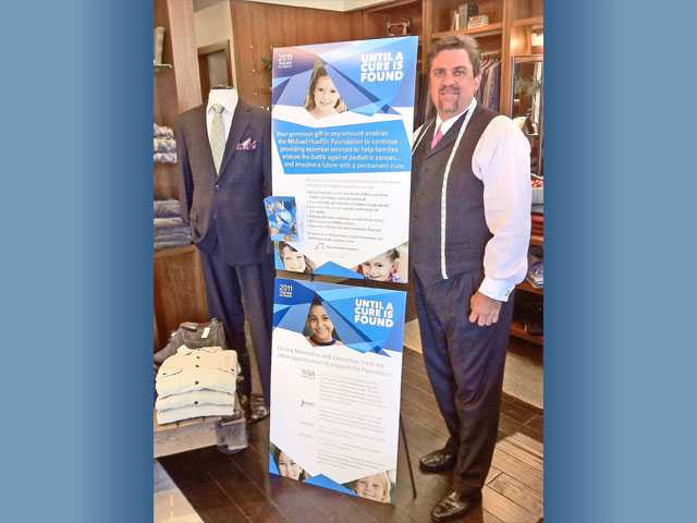 David Guenther, owner of J. David's, poses at the Valencia store with a sign promoting the Michael Hoefflin Foundation's year-end outreach drive with local businesses.