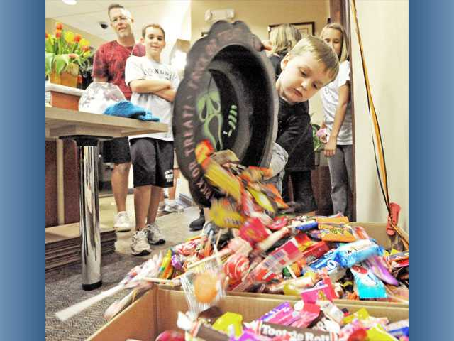 Storm Gibson, 3, dumps 5 pounds of candy into collection boxes during a candy buyback event held at the dental office of Drs. Kelly and Allen Smudde in Valencia on Tuesday.