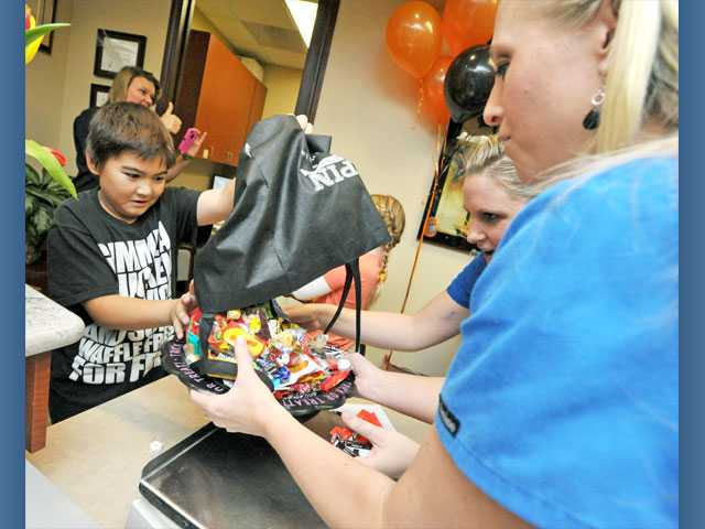 From left, John Csoti, 9, dumps his leftover Halloween candy to be weighed by marketing director Melissa Forness and office manager Janae Ree. The candy will be placed in care packages for troops overseas as part of Operation Gratitude.