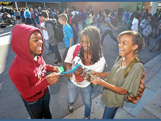 From left, eighth-graders Cedrinae Thompson, 13; Evony Herreres, 13; and Mckenzie Williams, 12, get to know each other by asking questions listed on strips of paper handed out for Mix It Up Day at Sierra Vista Junior High School in Canyon Country on Tuesday.