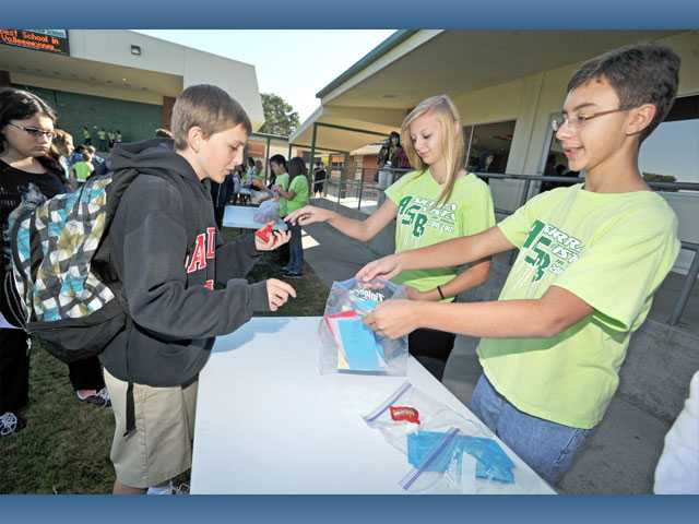 From left, eighth-grader Addason Dilley takes a bag of Skittles from Haylie Logan as Jeremy Rios, all 13, takes Dilley's completed slip of paper for Mix It Up Day.