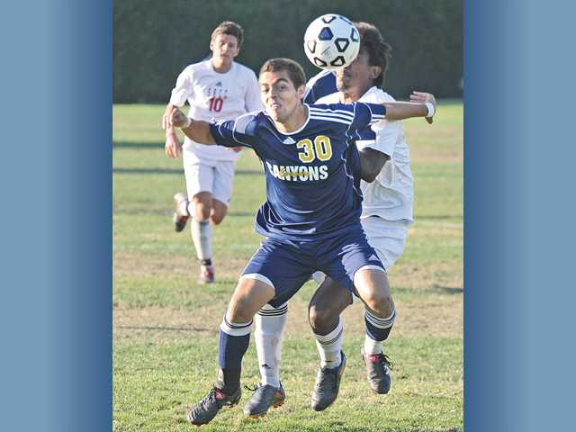 College of the Canyons Hany Helmy (30) heads the ball away from Santa Barbara City College's Jorge Gomez on Tuesday at College of the Canyons.