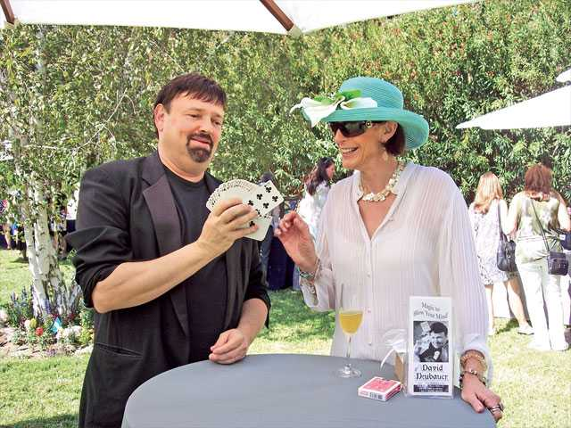 Left to right, Magician David Neubauer demonstrates a card trick to Jordana Capra.