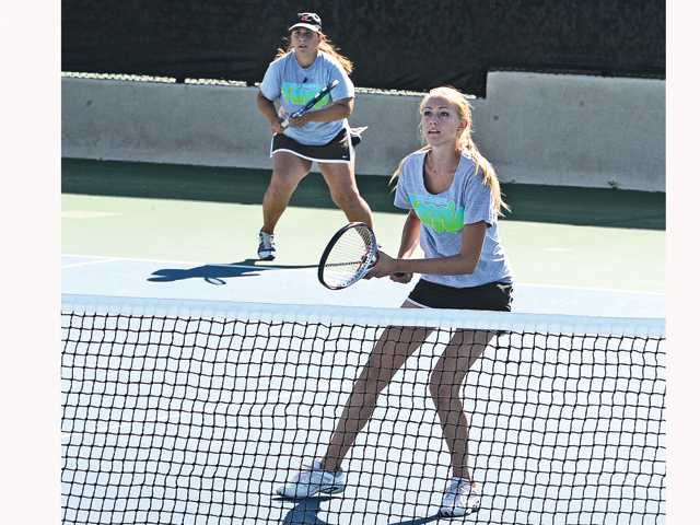 Valencia's Shenelle Trujillo, left, and Michelle Savage await the ball on Wednesday. They advanced to today's semifinals.