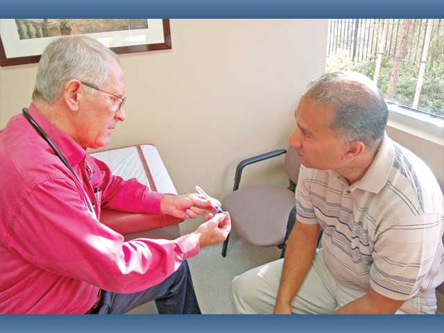 George Charnock, M.D., endocrinologist and staff physician at Henry Mayo Newhall Memorial Hospital, illustrates how to use Victoza, a medication for Type 2 diabetes, to patient Bala Balakumar at his Valencia office.