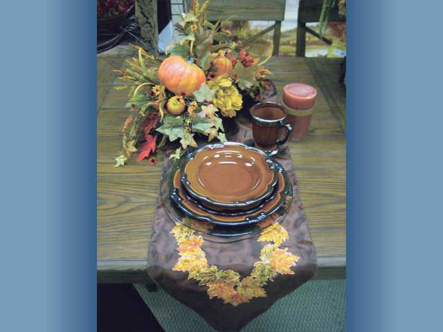 "Seasonal items for your Thanksgiving table: Table runner $23.99; Chris Madden ""Maison"" place setting, 16 pieces $59; clear, 12-inch charger $7.99; candle $10.99 and large arrangement $29.99."