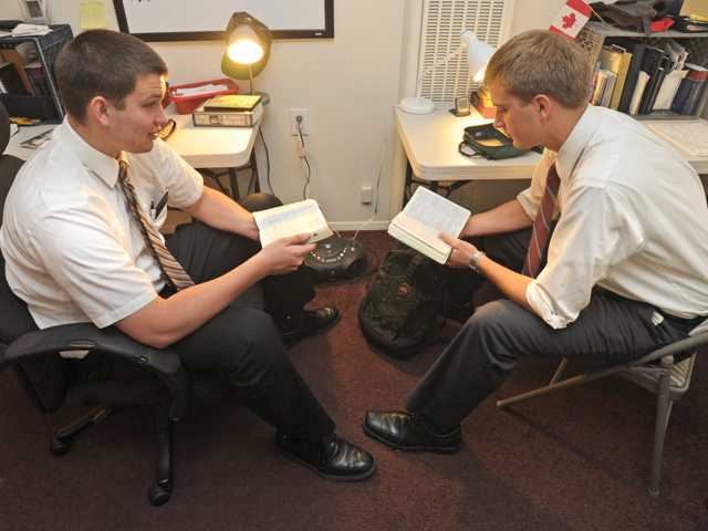 Twenty-year-old Mormon Missionaries Christopher Evanson, left, and Tyrell Nielson read passages from the Bible in their apartment in preparation for their work in their mission area in Newhall on Wednesday.