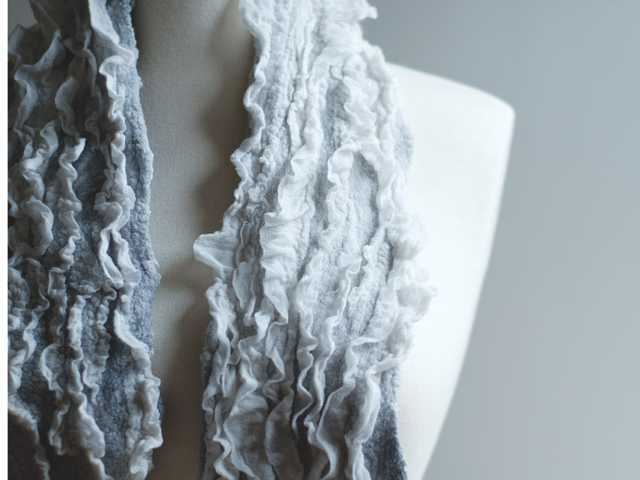 A scarf designed by Leah Adams of SpiderFelt. For this scarf, Adams, of Seattle, combined white ruffled bands of silk chiffon with painted silk and Merino wool roving in shades of stormy gray.