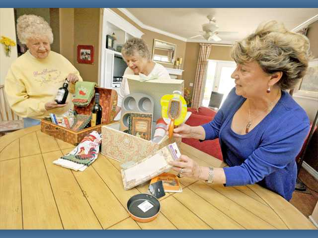From left, Charlotte Wilgus, Jacque Bunning and Anne Grandjean place items in boxes along with a cookbook of their personal recipes to benefit their missionary work in Uganda.