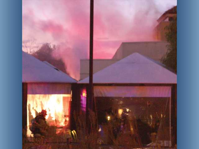 A firefighter works on a fire in the Valencia building where The Greens Sports Bar and Restaurant was formerly located.