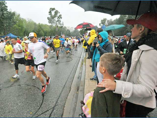 Spectators under umbrellas watch as runners begin the Santa Clarita Marathon along McBean Parkway in Valencia on Sunday.