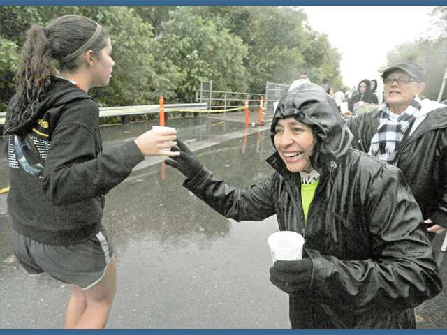 Gladys Olshevski, second from right, and Wendy Thrush, right, hand out water to runners on West River Trail.