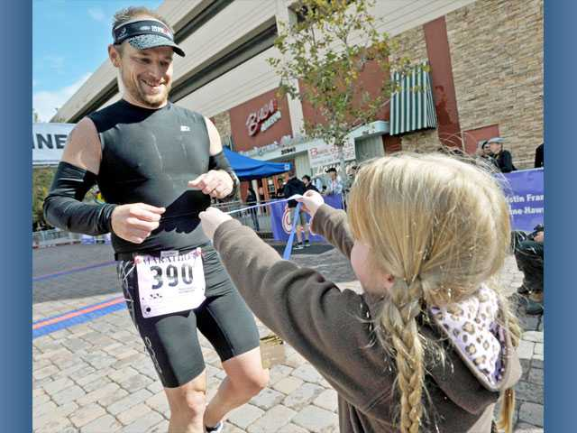 Georgia Poole, 6, greets her dad, Charles Poole, 41, of Palmdale, with a medal after he finishes the race.