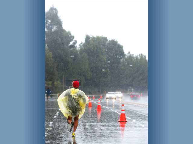 Dexter Emoto runs in the marathon as rain pours on McBean Parkway in Valencia.