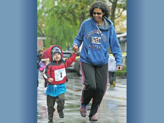 Kareem Farag, 3, and his mother, Lamia Farag, take part in the Kid K Fun Run on Town Center Drive.