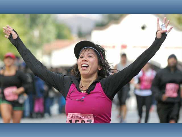 Hanh Ha celebrates after she finishes the Santa Clarita Half Marathon in Valencia on Sunday.