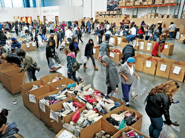 Hundreds of people sort through styles and sizes of shoes as thousands waited for hours outside to get sale prices on TOMS Shoes.
