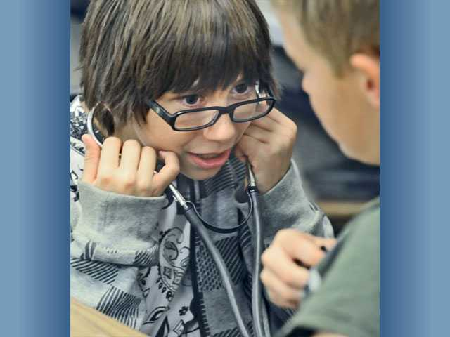 Fifth-grader Michael Tamez, left, uses a stethoscope to listen to the heart of classmate Dylan Baca as part of an interactive program focusing on the heart and its functions for fourth- and fifth-graders at Meadows Elementary School on Wednesday.