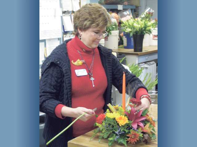Jan Hanauer, co-owner of Steve's Valencia Florist, works on a one-candle table setting for Thanksgiving.