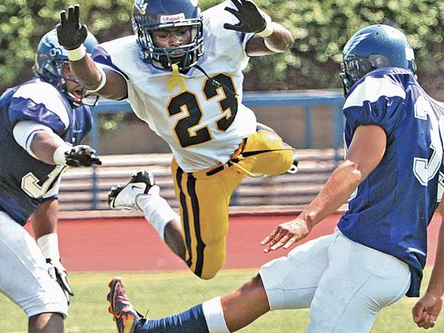 College of the Canyons cornerback Jabril Baldwin (23) tries to block an extra point attempt by Citrus College kicker Andres Magallon on Sept. 17.