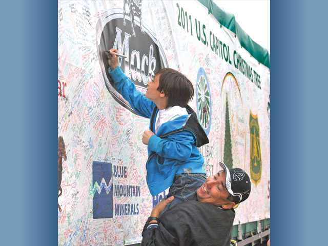 Quinn Hild, 9, is lifted by his father, Gary Hild, of Saugus, to autograph the cover of the trailer.