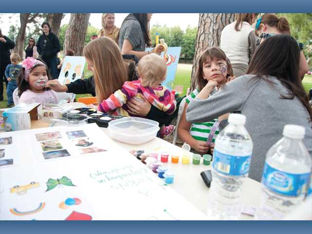 McGrath Elementary School teachers Jacque Norton, second from left, and Karla Valenzuela, right, paint the faces of Joselyn Sanchez, 5, and Katelyn Bischel, 8, at the school's Blue Ribbon Festival at Newhall Park on Sunday. Norton is also holding her daughter Emily.
