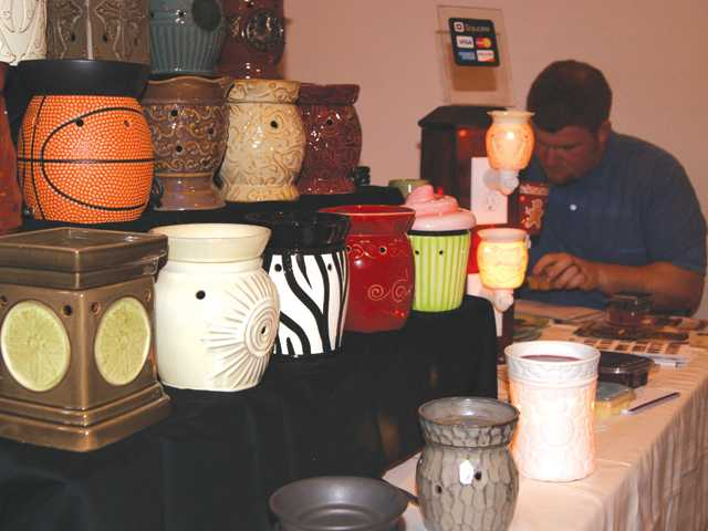 "Devin Mills prepares a ""warmer"" at a holiday boutique at Blessed Kateri Tekakwitha Catholic Church  in Santa Clarita. The warmers melt wax with a low-wattage lightbulb."