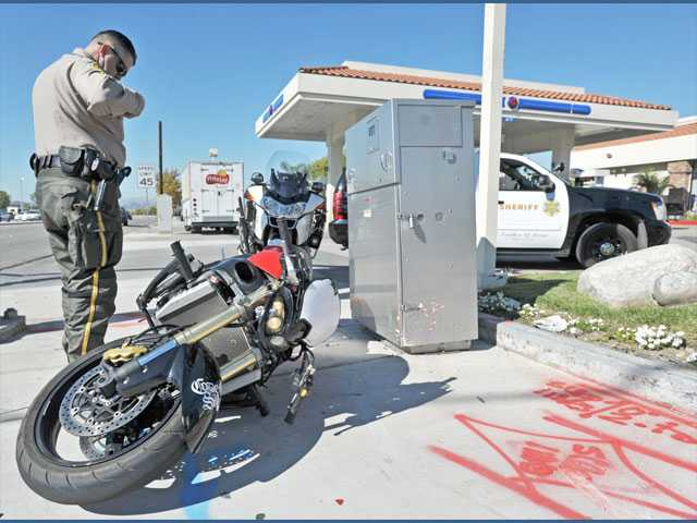 A sheriff's deputy investigates the scene where a suspected hit-and-run motorcyclist crashed his motorcycle and fled on foot outside the Arco gas station on Bouquet Canyon Road and Valencia Boulevard in Valencia on Monday.