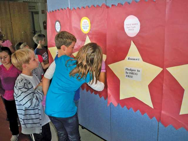 Students sign pledges to be drug-free to celebrate Red Ribbon Week.