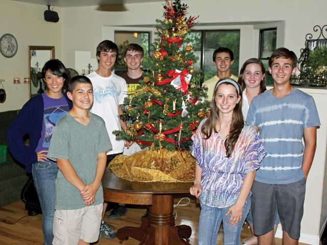From left, Hart Regiment members Chris Colangelo, Lis Sorensen, Eric VonRhein, Garett Dahl, Kelly Freet, Sam Beaty, Nick Vairo and Brianna Aboulache stand with the decorative tree the group donated to the Boys & Girls Club for the Festival of Trees benefit.