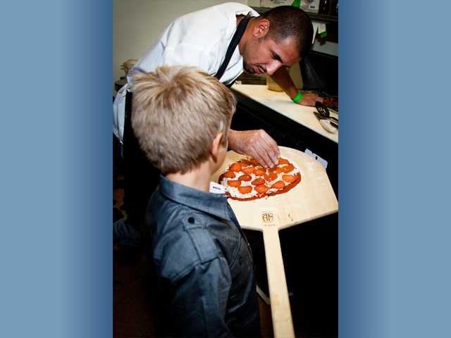 Chef Carlos of La Toscana shows a young birthday party guest how to add the finishing touches to a winning pepperoni pizza in the kitchen of the Valencia restaurant.