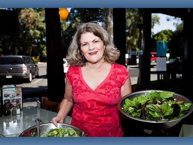Merry Graham holds two tantalizing La Toscana salads at her husband's soiree, ready to feed guests.
