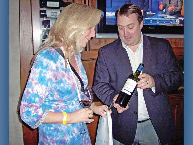 Eve Bushman examines a bottle of wine offered by Jean-Marc  Descabannes of Chateau Direct.