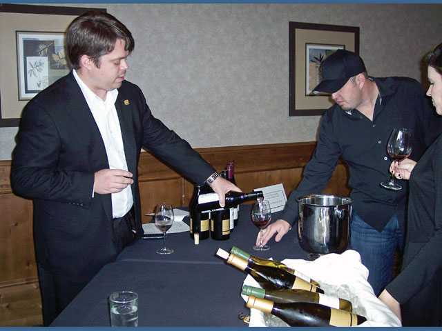 Brice Carson from American Wine and Spirits pours wine for guests at the annual Valencia Wine Co. Holiday Wine Tasting.