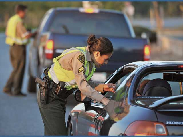Deputies Esmeralda Lopez, front, and Jeff Salveson, of the Sheriff's Department's Risk Management Bureau, check drivers' licenses and ask whether drivers have had anything to drink at a recent checkpoint on Valencia Boulevard, west of Bouquet Canyon Road, in Valencia.