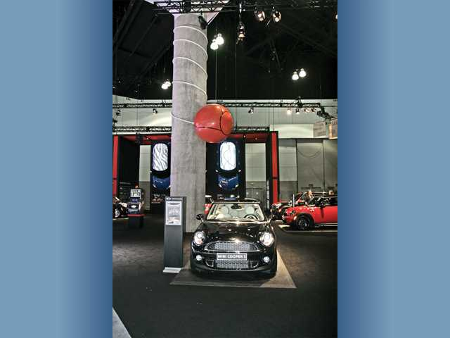 "The Mini Cooper display offered up a fun and youthful vibe at the L.A. Auto Show. A ""tetherball"" is wrapped around a cement pillar at the Los Angeles Convention Center in downtown Los Angeles."