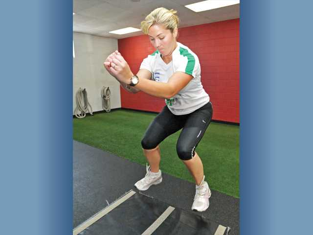 Megan Behounek practices box jumps on a padded platform while working out at Results Fitness in Newhall this week.