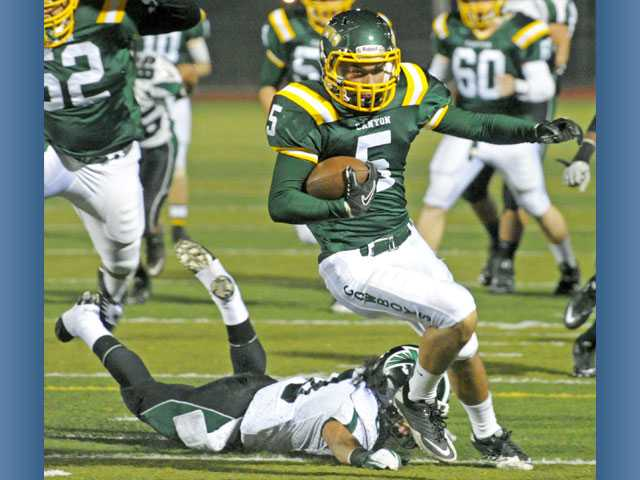 Canyon running back Daniel Castro (5) escaped the clutches of Palmdale's Mark Cisneros to score the Cowboys' first touchdown in the first round of the CIF-Southern Section Northern Division playoffs.