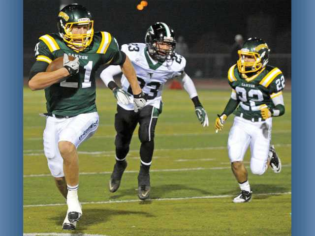Canyon's Drew Wolitarsky (21) speeds past Palmdale defensive back Jordan Zenno (23) as Cowboys teammate Zane Patterson (22) approaches on Friday at Canyon High.
