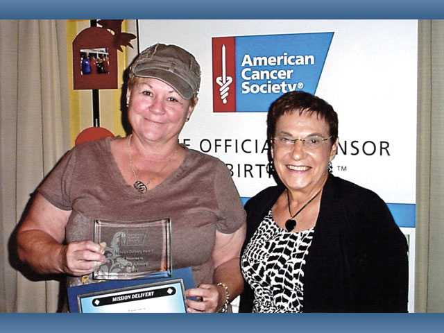 Donna Ashmore, left, is presented the Mission Delivery Award by Agnes Russell, who earned the Community Outreach Award at the 2011 Volunteer Tribute event.