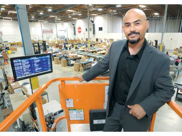 Michael A. Alvarez Jr., president of Deluxe Media Management, stands above the production floor recently in Valencia.  His company provides third-party logistics and marketing services to the entertainment industry.