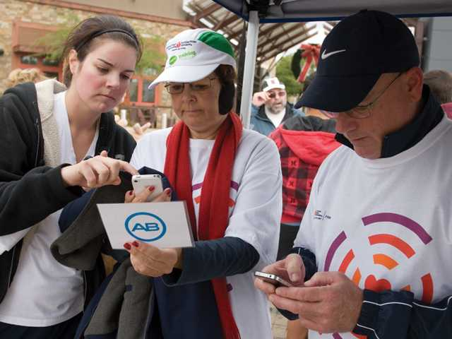Sarah Elroy, of Valencia, helps Susan Elroy text 10 people about the dangers of heart disease while teammate Bob Larlee also texts 10 people at the Advanced Bionics checkpoint at Westfield Valencia Town Center on Sunday.