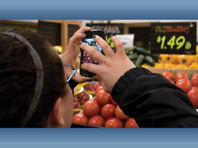 Stephanie Jimenez, of Castaic, photographs tomatoes inside Sprouts Farmers Market. The Sprouts challenge asked participants to spell out words with photographs of fruits and vegetables.