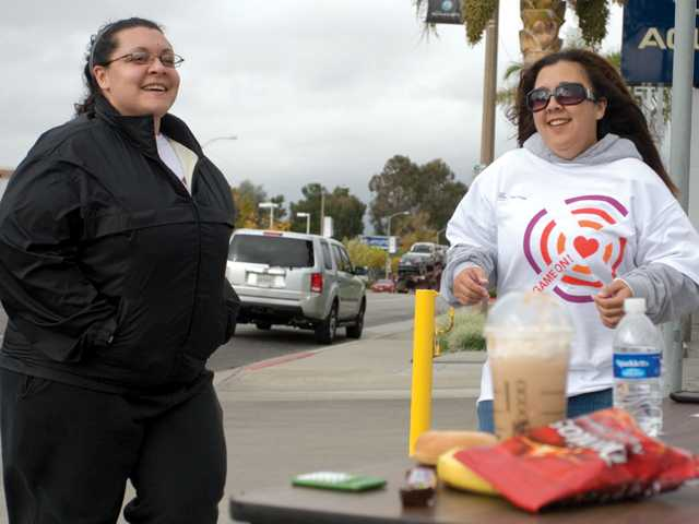 Jimenez and Stephanie Struyck jog in place in front of the Valencia Acura car dealership. The challenge asks participants to guess the sum of calories of the food items on the table, and then make up the difference with the actual sum in steps.