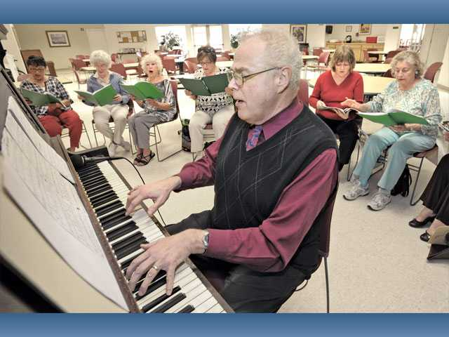 "SCV Senior Center music director John Swinford accompanies Silver Belles as they rehearse ""Frosty The Snowman"" in the multipurpose room at the Bouquet Canyon Senior Apartments in Santa Clarita on Thursday."