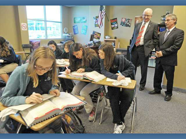 Students work in Kathleen Stift's math class as principal Edward Gika, right, takes McKeon on a tour.