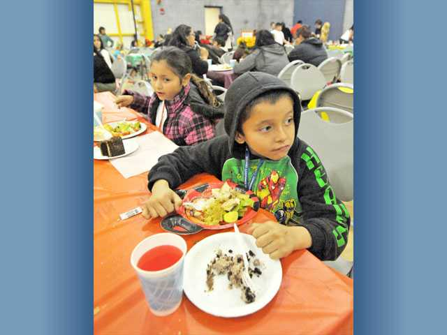 Marco Bustillos, 7, front, and Gally Delatorre, 8, both of Newhall, enjoy dinner and cake at the community Thanksgiving dinner held at the Santa Clarita Community Center in Newhall on Monday.